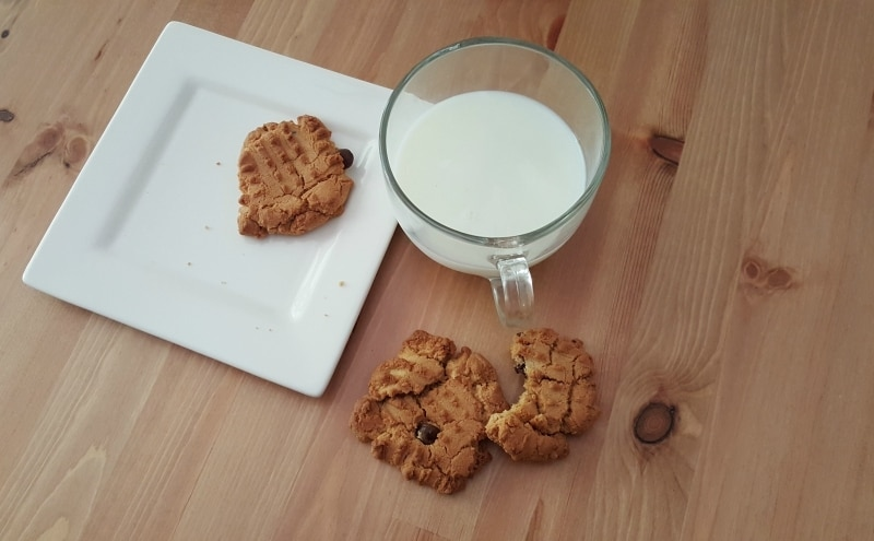 half eaten peanut butter cookie on table with milk