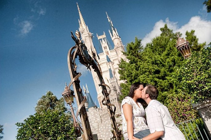 couple kissing in front of cinderella castle