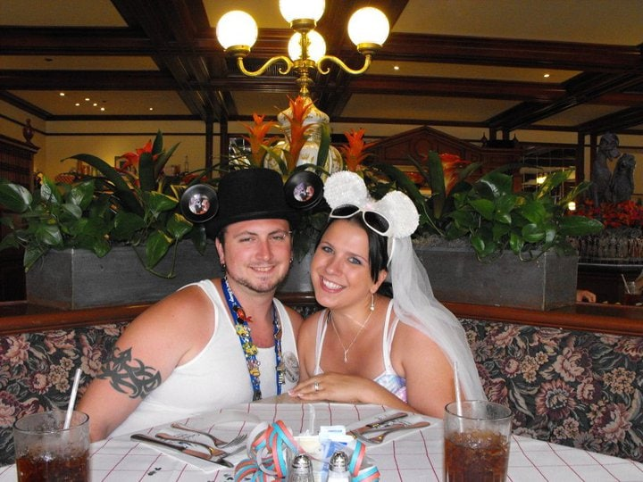 couple together in disney honeymoon ears at restaurant