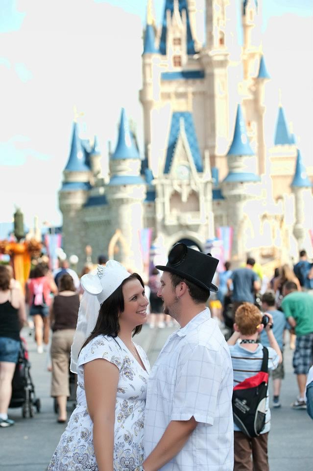 newly wed couple in honeymoon mickey ears in front of cinderella castle