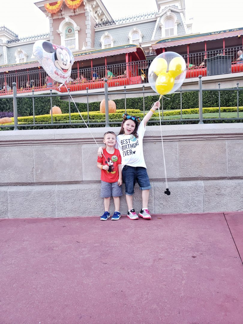 Front of Magic Kingdom, two kids holder a Mickey Mouse balloon. Smiling and feeling happy.