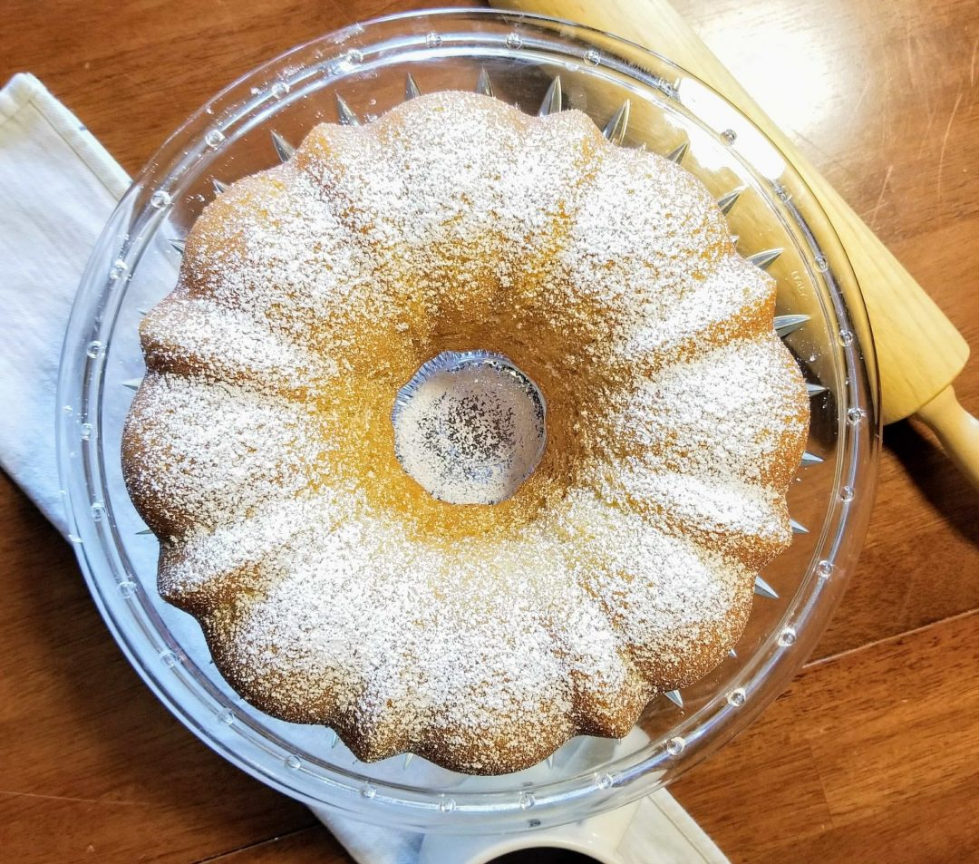 bundt cake on clear cake pedestal on wooden table with wooden rolling pin and white towel