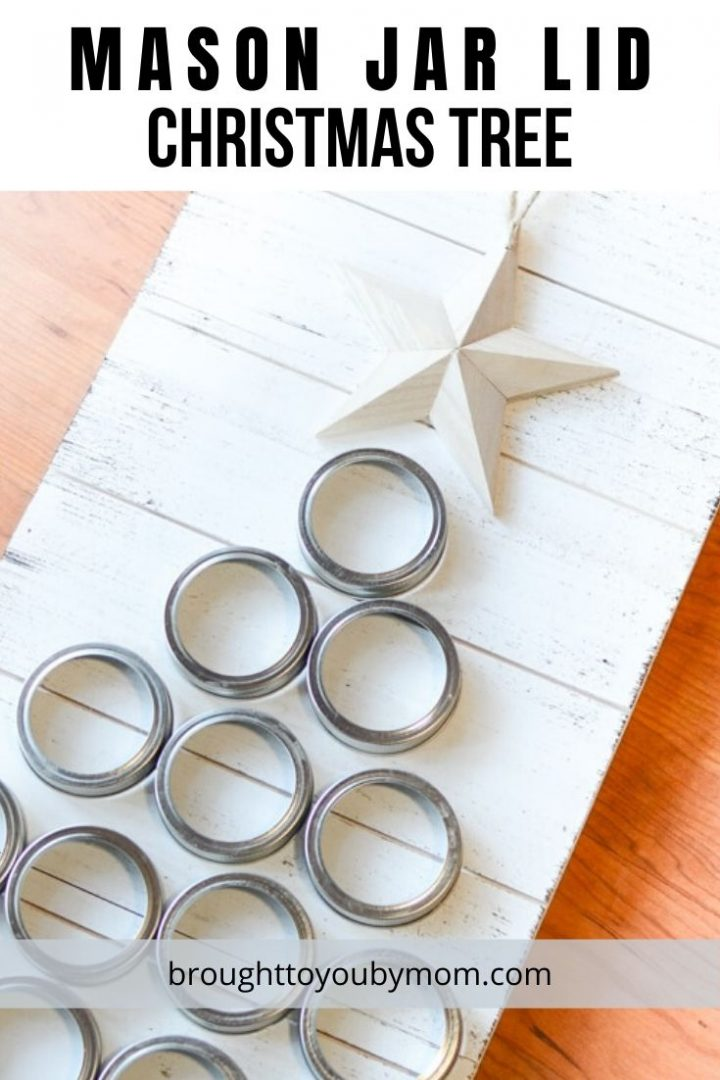 mason jar lids creating a christmas tree on a white wooden board