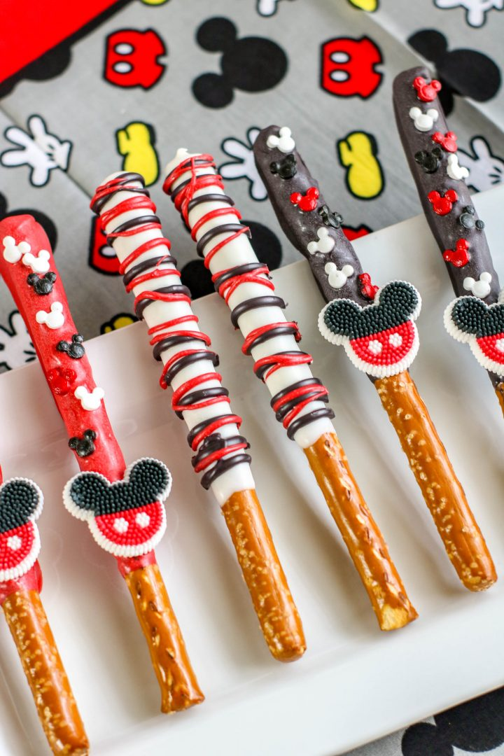 pretzel rods decorated with mickey mouse candy and drizzled with chocolate