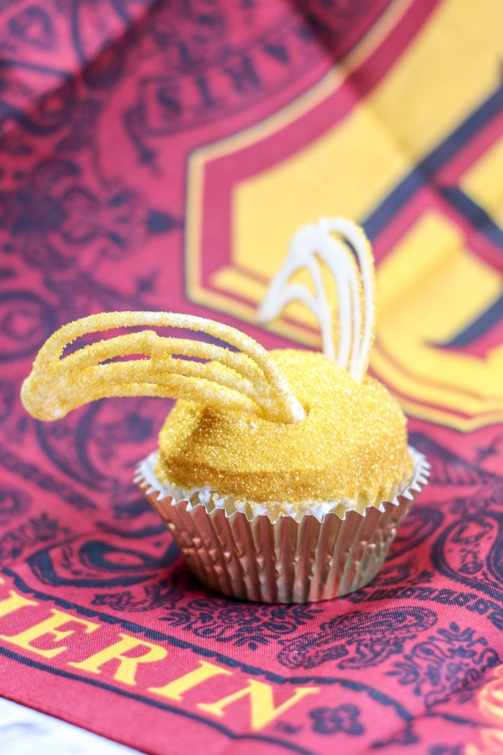 golden snitch cupcake on hogwarts themed background