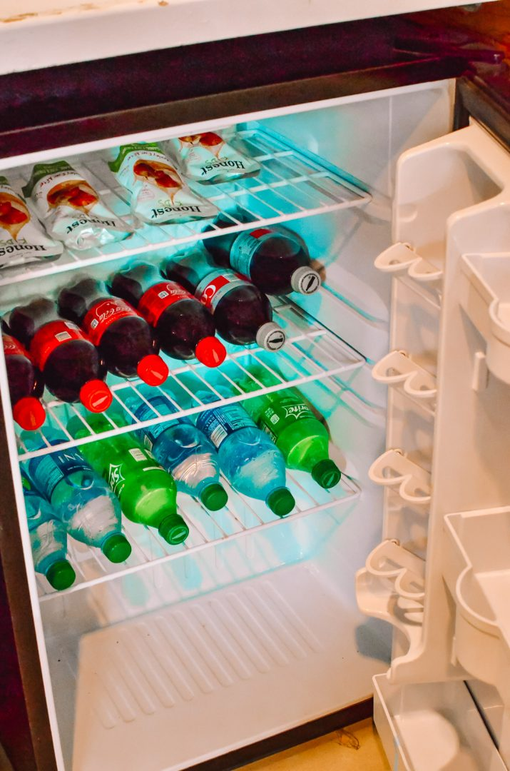 Fridge filled with soda, water, and juice.