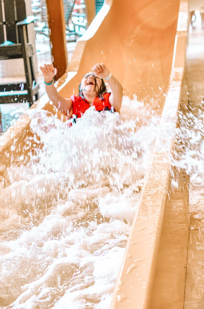Girl excited and happy while coming down water slide at Great Wolf Lodge