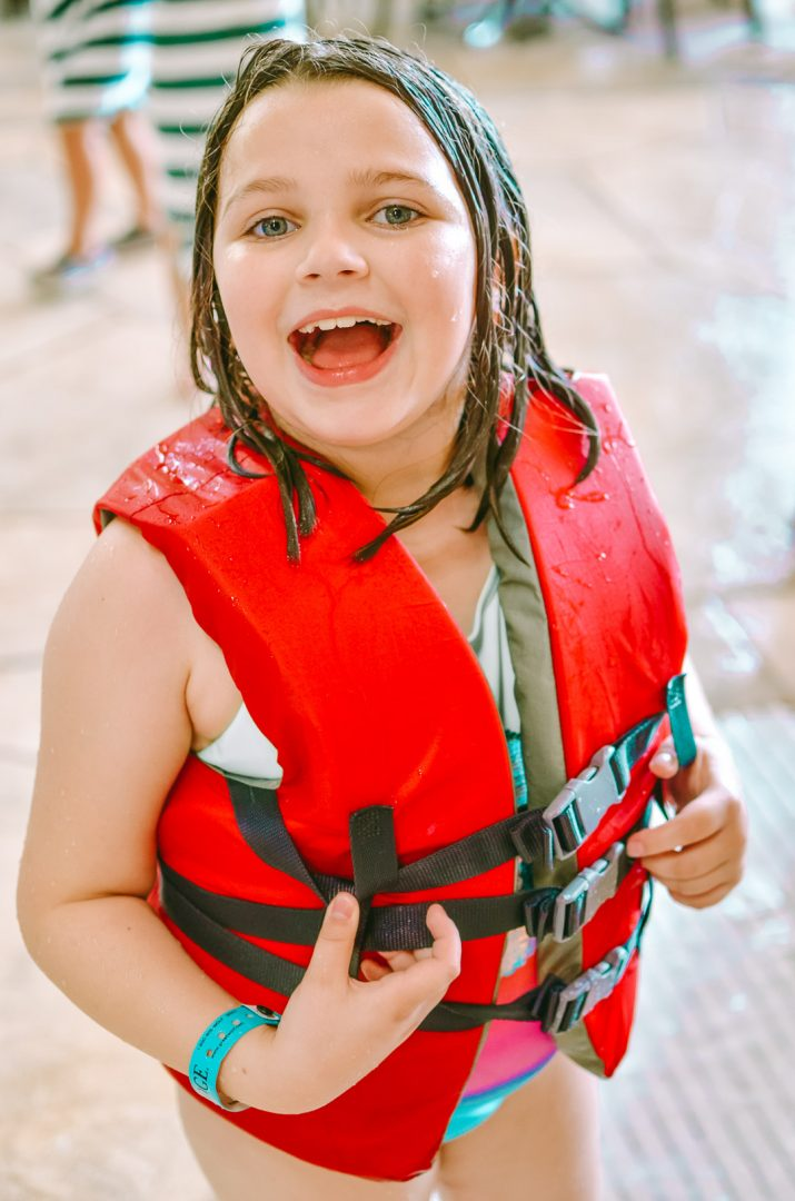 Young girl in life vest smiling at Great Wolf Lodge