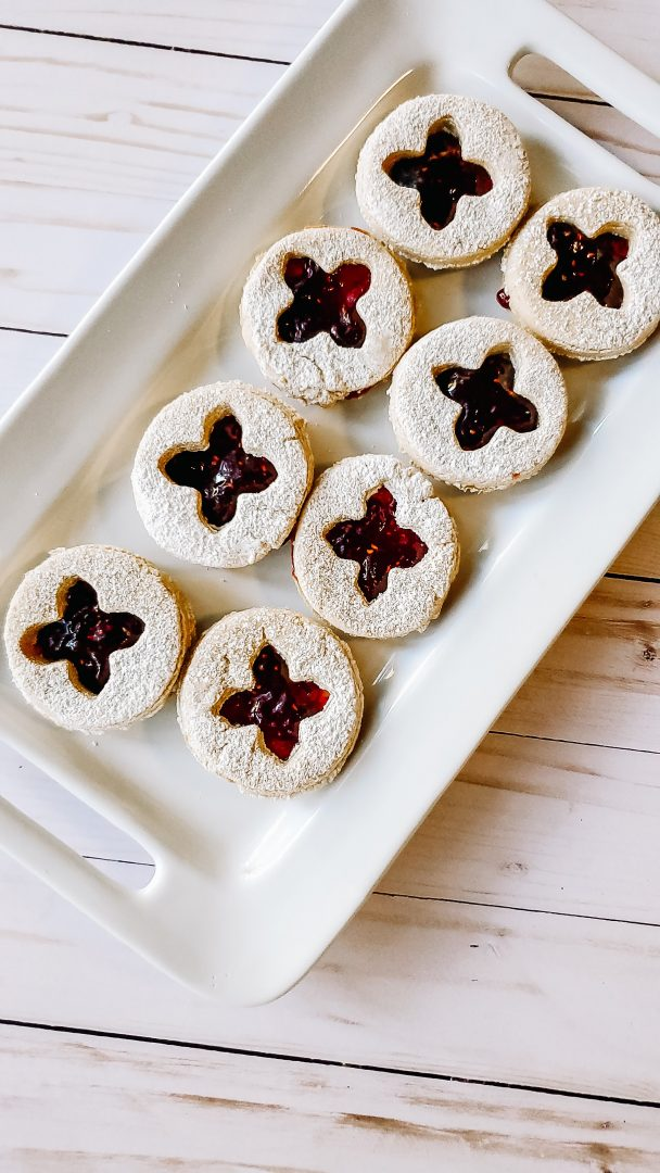 linzer cookies on white serving platter on white wood