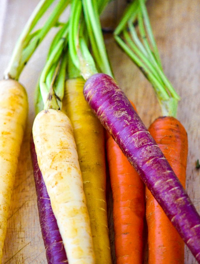 colorful organic carrots on cutting board