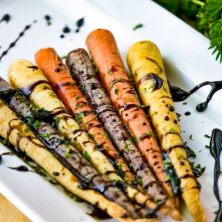 roasted carrots on white dish with greens