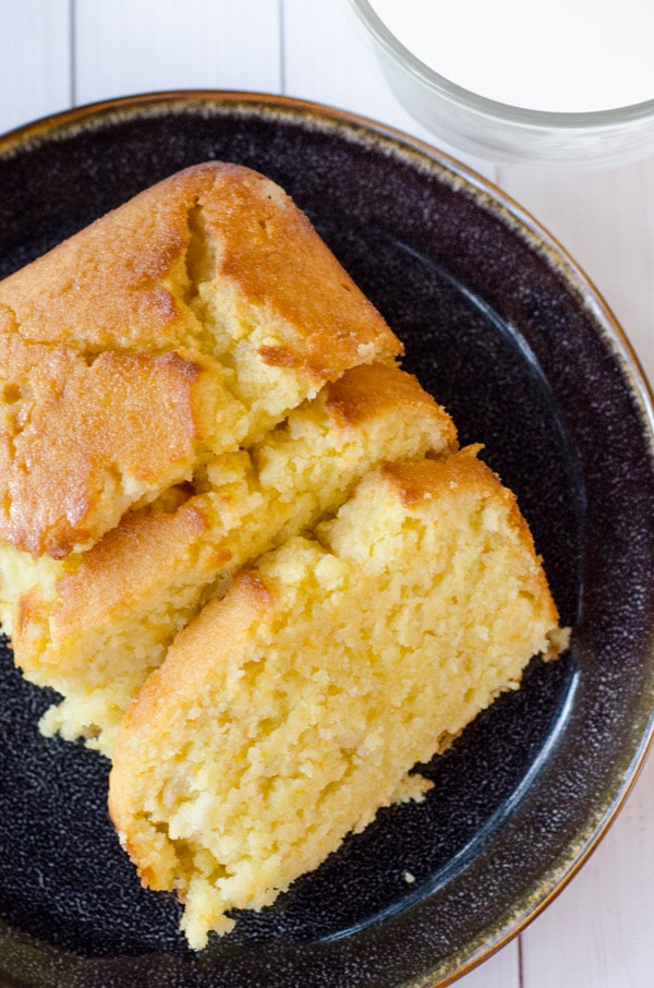 tangerine drizzle cake on black plate with milk