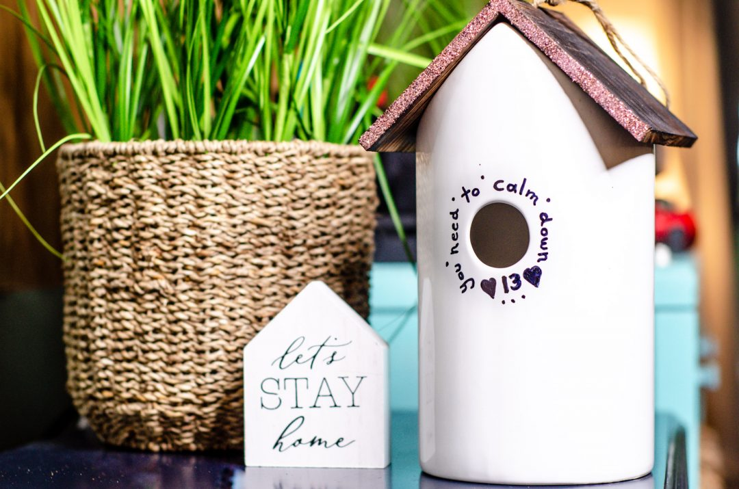 ceramic birdhouse next to green plant
