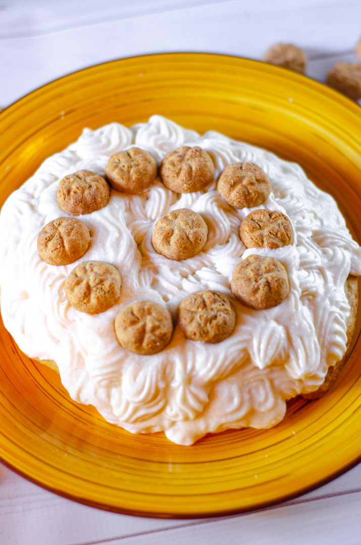 dog cake covered in white frosting on yellow plate