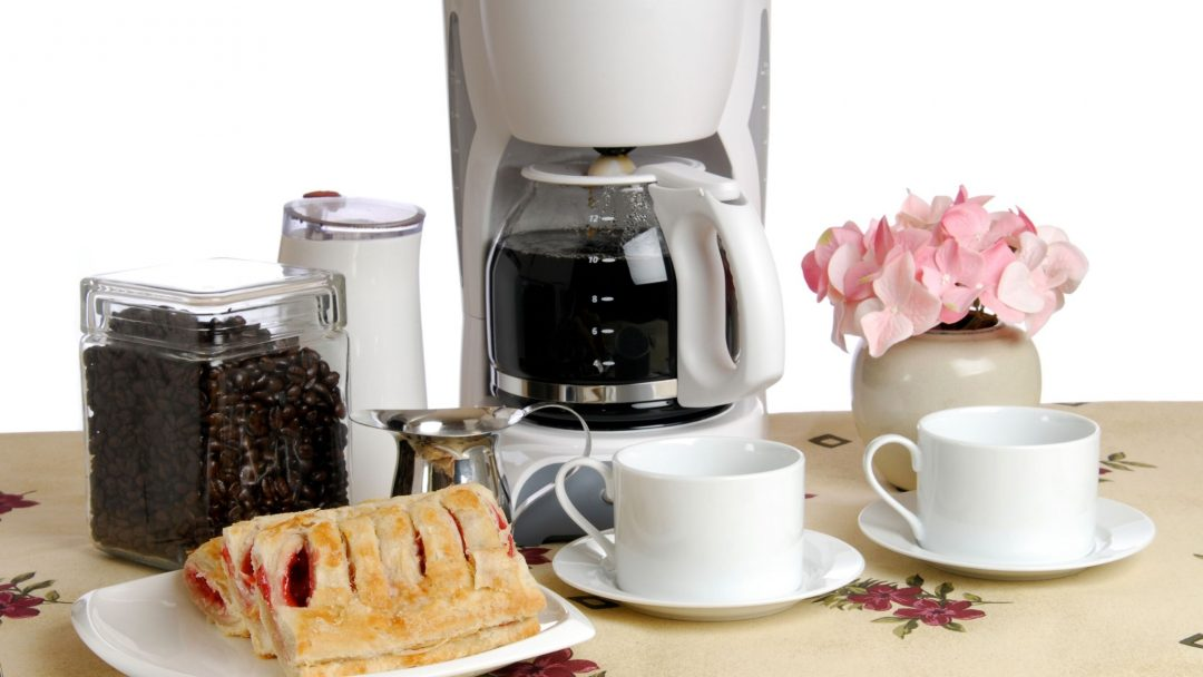 coffee maker with pastry and coffee mug