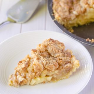 slice of apple crumble pie on white plate with pie server