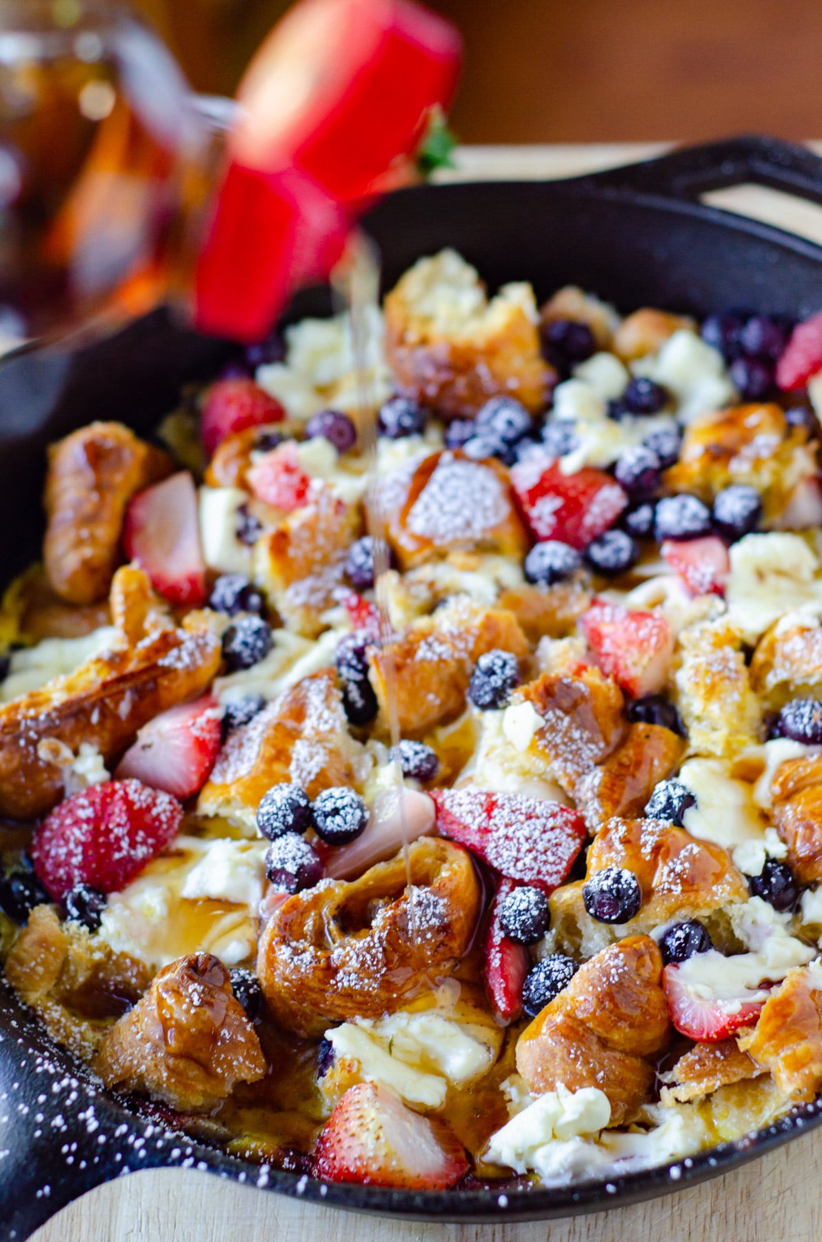 Breakfast Casserole mixed with berries and croissants in a cast iron skillet with maple syrup being poured over.