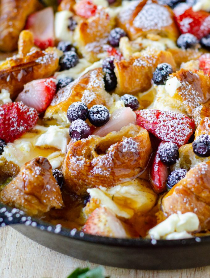 blueberry and strawberries cut into a casserole dish with croissants